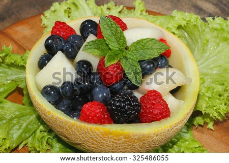Melons bits, raspberries, blackberries and blueberries in a halved and hollowed Galia melon, garnished with mint