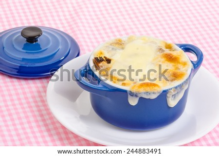 Melted cheese baked golden brown  pouring over edge of blue bowl  of French Onion Soup.  Strong light from behind blue bowl sitting on pink gingham tablecloth. - stock photo