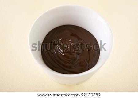 Melted chocolate sauce in a small white bowl. - stock photo