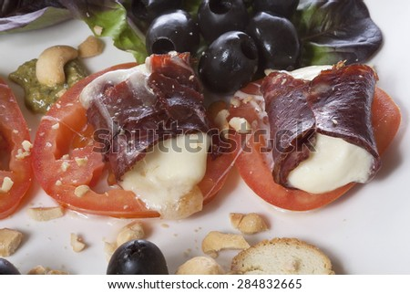 Melted mozzarella in beef prosciutto served on a white plate with tomatoes, olives and bruschetti. Isolated on white. - stock photo