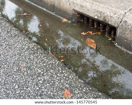Melted water flows down through the manhole - stock photo