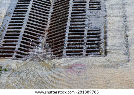 Melted water flows down through the manhole cover on a sunny day - stock photo