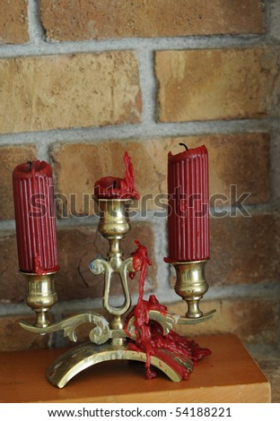 Melted wax candle with red wax dripping down an old golden brass candle holder. - stock photo