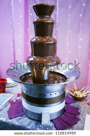 Melting chocolate drips down the different tiers of a chocolate fountain structure. - stock photo
