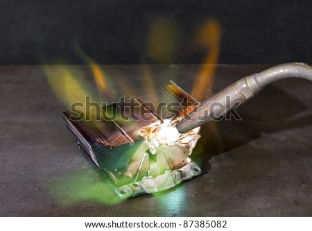 melting heat sink and welding torch on metallic ground - stock photo