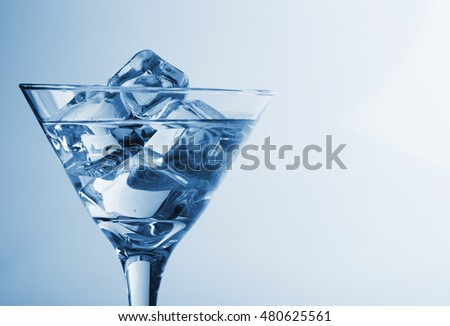 melting ice cubes and glass of alcohol studio shot