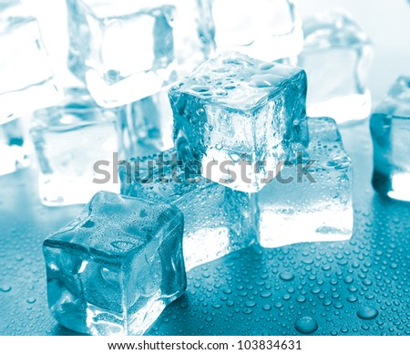 melting ice cubes on glass table. - stock photo