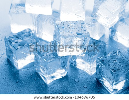 melting ice cubes on glass table - stock photo