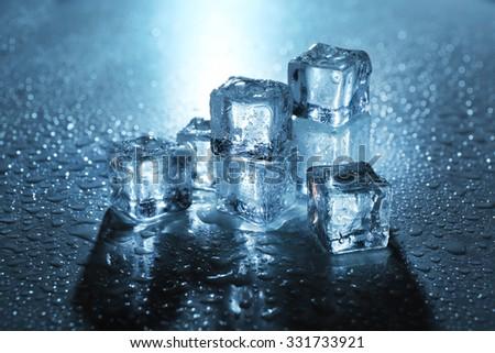 Melting ice cubes under blue light, close up - stock photo