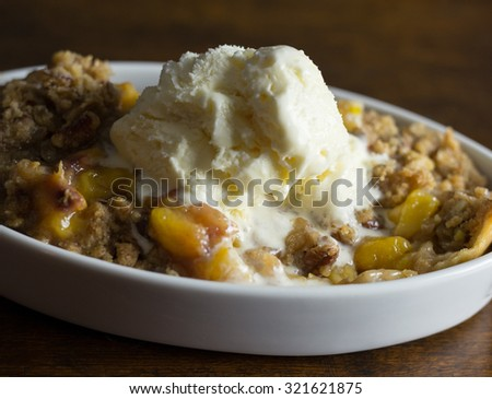 Melting scoop of vanilla ice cream on top of peach cobbler with pecans.  - stock photo