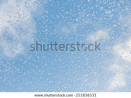 Melting snow drops blue sky background and frozen water texture, condensation on window glass, transparent glass in winter and ice with white snow in contact with morning warm sunlight. Horizontal - stock photo