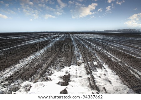 Melting snow in a plowed field - stock photo