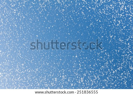 Melting snow spots blue sky background and frozen water texture, condensation on window glass, transparent glass in winter and ice with white snow in contact with morning warm sunlight. Horizontal - stock photo