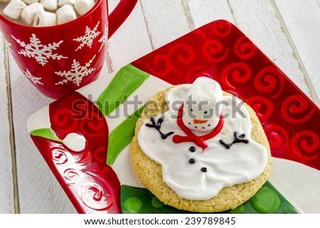 Melting snowman sugar cookie sitting on snowman holiday plate with snowflake mug filled with hot chocolate and marshmallows