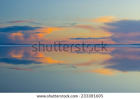Melting spring mountain lake in the setting sun. - stock photo