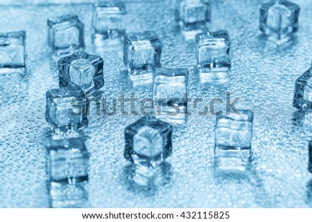 Melting transparent blue ice cubes on glass - stock photo