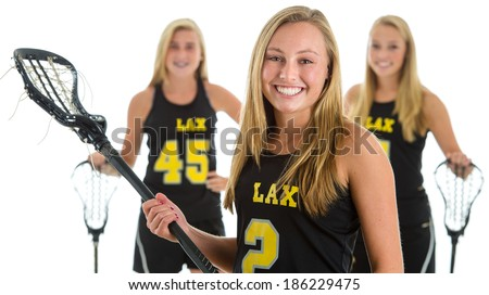 Members of a girls lacrosse team. Focus on woman in front, teammates soft focused in background. Studio shot, isolated on white background. - stock photo