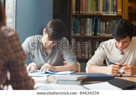 Members of a study group working in a library - stock photo