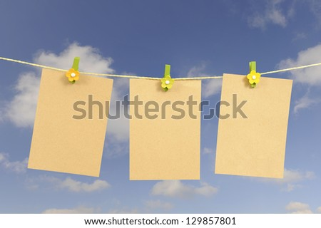 memo notes hanging on a clothes line against a blue sky with clouds