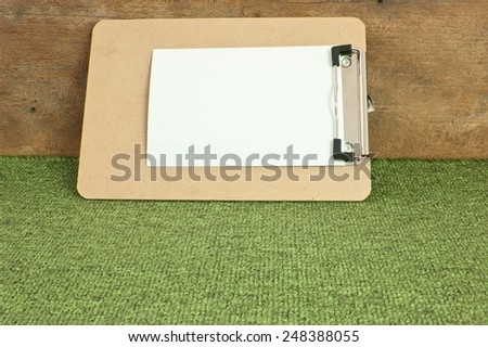 Memo Pad brown corrugated pattern on green carpet. - stock photo