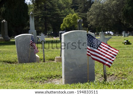 Memorial Day flags placed at the grave sites to pay tribute to fallen servicemen and women who gave their lives in service to our country - stock photo