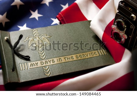Memorial Day remembrance photo of a World War II  Military Service photo album and antique camera with United States Flag as a background symbolizes memories of a war veteran's military service. - stock photo