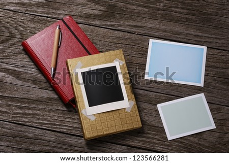 Memory and attention symbols and blank instant photos on wooden background - stock photo