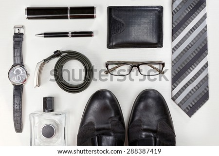 Men accessories. Black elegant accessories pieces isolated on white wooden table. Top view. - stock photo