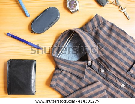 Men accessories: shirt, razor, pen,wallet,watch, and keys on the  wood background.  - stock photo