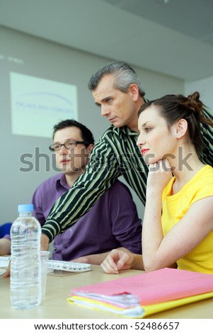 Men and a woman in front of a laptop computer