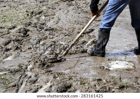 Men and equipment cleaning up after the mudslides - stock photo