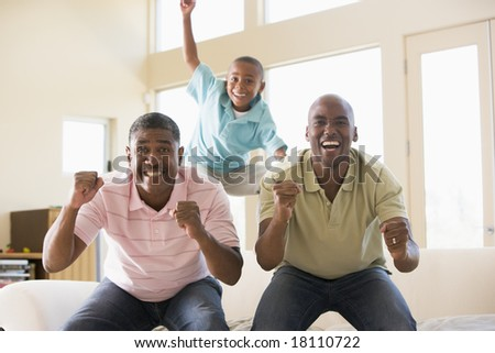men and grandson cheering at television - stock photo