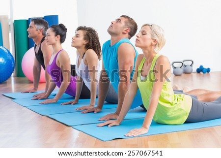 Men and women doing yoga stretch in gym class - stock photo