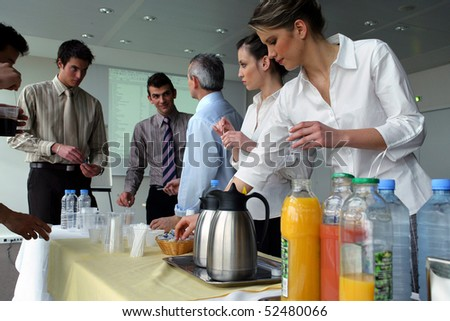 Men and women having a drink at work - stock photo