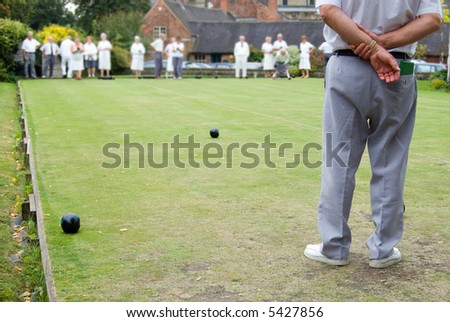 Men and women playing Flat Lawn Bowls. Focus on the man in the foreground - stock photo
