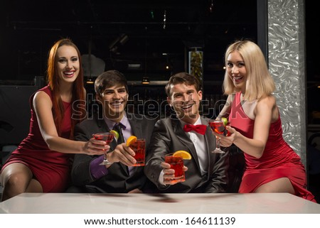 Men and women raised their glasses with cocktails in a nightclub, a party with friends - stock photo