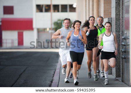 Men and women running for exercise downtown - stock photo