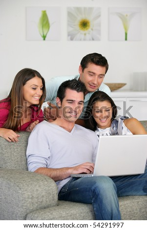 Men and women smiling in front of a laptop computer