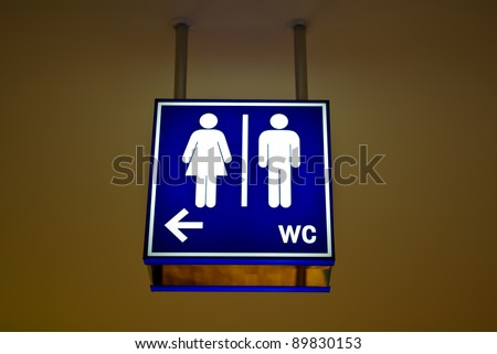 Men and women toilet sign with an arrow showing direction