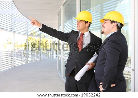 Men architects on building construction site working - stock photo