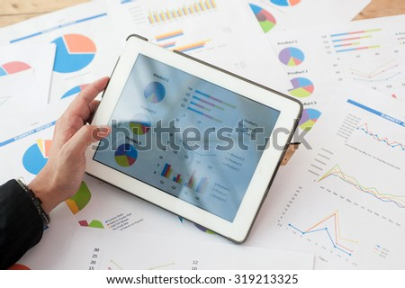 Men are opening the Tablet viewing graphs and statistical research has financial reports as background. - stock photo