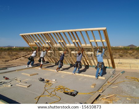 Men are working on building a wall of a house.  They are looking at their work with their backs facing the camera.  Vertically framed shot. - stock photo