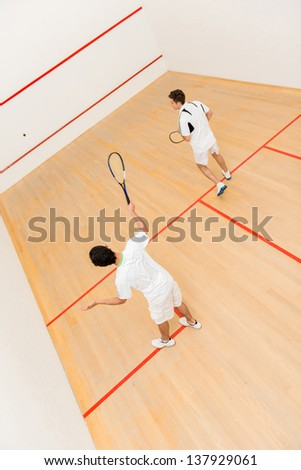 Men at the court playing a match of squash - stock photo