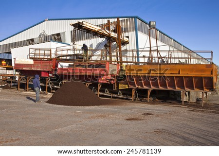 Men at work processing compost for plants at a nursery farm. - stock photo