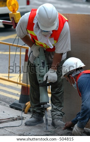 men at work with a jackhammer for roadworks - stock photo