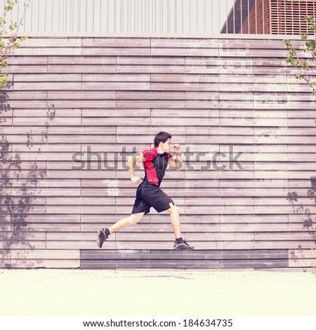 Men athlete running next to some city wall - stock photo