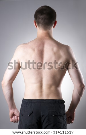 Men back close-up on a gray background - stock photo
