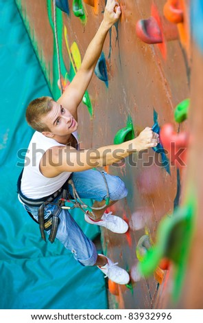 men climbing on a wall in an outdoor climbing center - stock photo