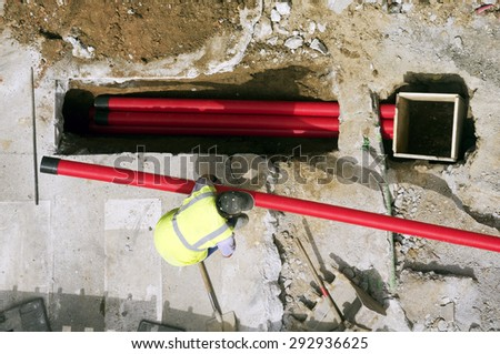 men construction worker  repair  corrugated conduit  pipes in construction site - stock photo