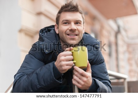 Men drinking coffee. Handsome young men drinking coffee outdoors - stock photo